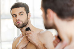 Shaving procedure. Rear view of handsome young man shaving his face with electric shaver while standing in front of the mirror Royalty Free Stock Photos