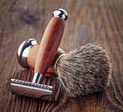 Shaving razor and brush. Wooden shaving razor and brush on wooden background stock image