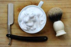 Shaving razors, brush and bowl with foam. Royalty Free Stock Photography