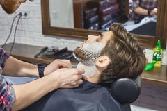 Shaving with a straight razor in the Barber shop Stock Image