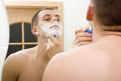 Shaving young man in the bathroom's mirror Royalty Free Stock Photos