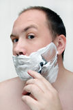 Shaving. The young man has a shave royalty free stock photo