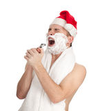 Shaving young man in red Christmas hat Stock Photos