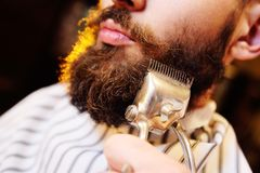 Shaving your beard in barbershop. Barber makes a styling beard to the client - a young handsome man with a mustache. Shaving your beard in barbershop royalty free stock photos
