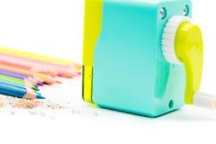Shavings för vässare för pastellblåttguling roterande med träfärgrika blyertspennor som isoleras på vit bakgrund, tillbaka till s Arkivbild
