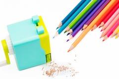 Shavings för vässare för pastellblåttguling roterande med träfärgrika blyertspennor som isoleras på vit bakgrund, tillbaka till s Royaltyfria Foton
