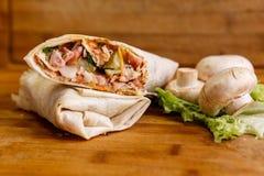 Shawarma三明治-稀薄的lavash皮塔饼面包新卷用烤肉,蘑菇,乳酪,圆白菜,红萝卜,调味汁, g填装了 免版税库存照片