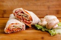 Shawarma三明治-稀薄的lavash皮塔饼面包新卷用烤肉,蘑菇,乳酪,圆白菜,红萝卜,调味汁, g填装了 免版税图库摄影