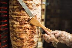 Shawarma και ciabatta μαγειρέματος σε έναν καφέ Ένα άτομο στα μίας χρήσης γάντια κόβει το κρέας σε ένα οβελίδιο στοκ φωτογραφία με δικαίωμα ελεύθερης χρήσης