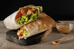 Shawarma with chicken and tomato. Put on a wooden background stock image