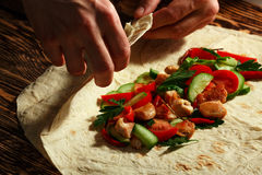 Shawarma. Cooking traditional shawarma wrap with chicken and vegetables royalty free stock photo