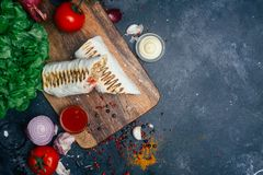Shawarma di kebab di Doner o involucro del doner Pollo grigliato sul pane della pita del lavash con gli ortaggi freschi - pomodor fotografia stock libera da diritti