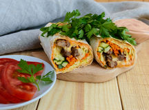 Shawarma - Middle East (Arabic) dish of pita (lavash) stuffed with: grilled meat, sauce, vegetables. Stock Photography