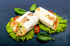 Shawarma - Middle Eastern dish made from lavash pita, stuffed with chicken, mushrooms, fresh vegetable salad, sauce. Serving on lettuce leaves on a black Stock Image
