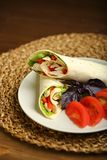 Shawarma, roll with chicken, salad in pita bread. Shaurma without sauce with chicken, pepper, lettuce. Low-calorie roll from pita bread, next to purple basil and Stock Photography