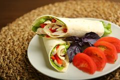 Shawarma, roll with chicken, salad in pita bread. Shaurma without sauce with chicken, pepper, lettuce. Low-calorie roll from pita bread, next to purple basil and Royalty Free Stock Photo