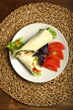 Shawarma, roll with chicken, salad in pita bread. Shaurma without sauce with chicken, pepper, lettuce. Low-calorie roll from pita bread, next to purple basil and Royalty Free Stock Photos