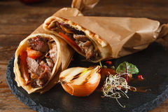 Shawarma rolled in baking paper on plate Stock Photo