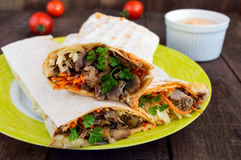 Shawarma sandwich - fresh roll of thin lavash pita bread filled with grilled meat, mushrooms, cheese, cabbage, carrots, sauce, g Royalty Free Stock Photo