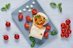Shawarma sandwich or lavash snack with fresh vegetables on the gray plate decotated with cherry tomatoes, basil leaves, sauce. On the gray concrete background Stock Photos