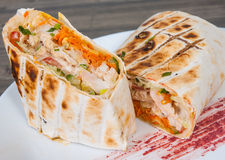 Shawarma in thin pita bread with chicken and vegetables Stock Photo