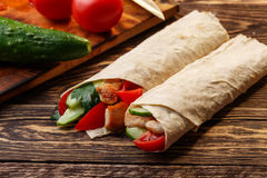 Shawarma. Traditional shawarma wrap with chicken and vegetables near its ingredients stock photography
