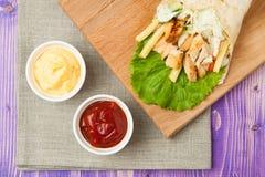 Shawarma y tazas árabes con la salsa de tomate y el queso en la tabla Imagenes de archivo