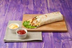 Shawarma y tazas turcos con la salsa de tomate y el queso en la tabla Fotografía de archivo libre de regalías