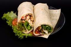 Shawarmas on lettuce. On a black background stock image