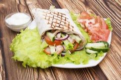 Shawarmas på grönsallat isolerade en träbakgrund Arkivfoton