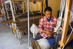 Shawl manufacturing. A local weaver is weaving woolen shawl for tourists with manual hand weaving machines at a Govt. undertaking weaving center near Manali Royalty Free Stock Photo