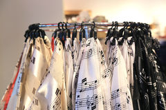 Shawls with musical notes hanging on hooks Royalty Free Stock Photos