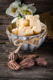 Shea butter amd shea nuts. A cup full with shea butter with shea nuts on a rusty table stock images