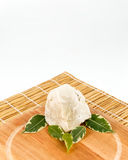 Shea butter lying on the wooden board, stands on the straw mat,. Unrefined, organic Shea butter with green leaves laying on the wooden board which is laying on Royalty Free Stock Photography