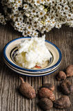 Shea butter and nuts. On a wooden table with flowers in the background royalty free stock image