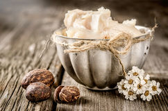 Shea butter and nuts. On a wood Royalty Free Stock Photography