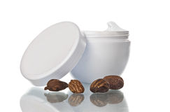Pot of shea butter and nuts. Shea butter in a pot and nuts, white background and reflection Royalty Free Stock Images