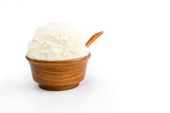 Shea butter in the wooden bowl, clean white background. Unrefined, organic Shea butter in the wooden bowl with the spoon, standing on the clean white background Stock Image