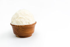 Shea butter in the wooden bowl, clean white background. Unrefined, organic Shea butter in the wooden bowl standing on the clean white background Royalty Free Stock Images