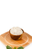 Shea butter in the wooden bowl stands on the wooden board, on th. Unrefined, organic Shea butter in the wooden bowl and with green leaves stands on the wooden Royalty Free Stock Photography