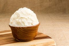 Shea butter in the wooden bowl stands on the wooden board, on th. Unrefined, organic Shea butter in the wooden bowl, stands on the wooden board, jute fabric Stock Image
