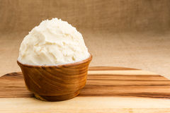 Shea butter in the wooden bowl stands on the wooden board, on th Royalty Free Stock Images