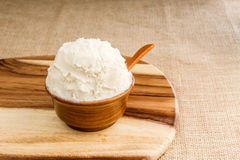 Shea butter in the wooden bowl stands on the wooden board, on th. Unrefined, organic Shea butter in the wooden bowl with the spoon, stands on the wooden board Royalty Free Stock Photography