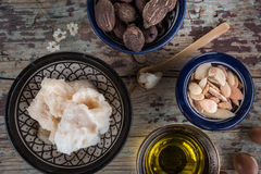 Shea nuts anbutter and argan oil and seeds. Shea butter and nuts and argan fruits and oil on a wooden table Stock Photography