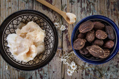 Shea nuts and shea butter on a wooden top. Shea butter and nuts on wood, flat lay royalty free stock image
