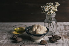 Shea oil and butter with shea nuts. Two bowl of shea butter and oil with shea nuts on shabby wooden table Stock Image