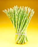 Sheaf of asparagus on a yellow background. Royalty Free Stock Image