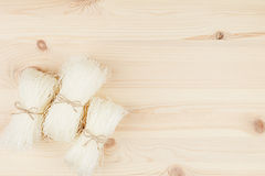 Sheaf raw asian cellophane noodles on beige wooden board with copy space, top view. Royalty Free Stock Images