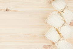 Sheaf raw asian cellophane noodles on beige wooden board with copy space, top view. Royalty Free Stock Image