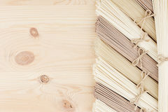 Sheaf raw asian noodles on soft beige wooden board with copy space, top view. Sheafs raw asian noodles soft beige wooden board with copy space, top view Stock Image